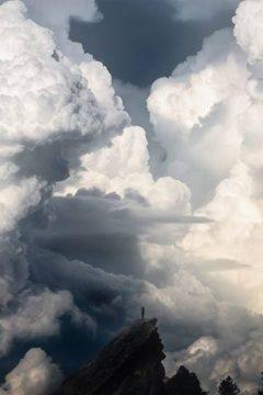 человек на скале, над ним громадные суровые облака