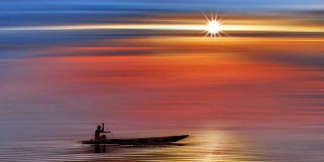 лодка в бескрайнем море на закате