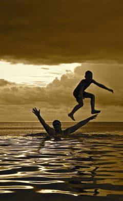 мужчина подбрасывает сына над водой