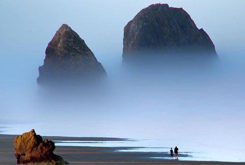 люди идут к скалам, возвышающимся над полосой тумана
