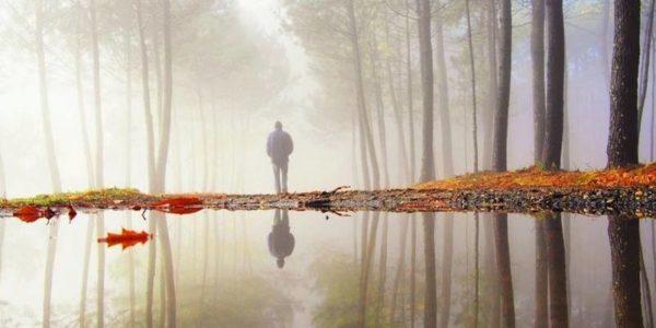 Мужчина задумчиво стоит, отражаясь в воде