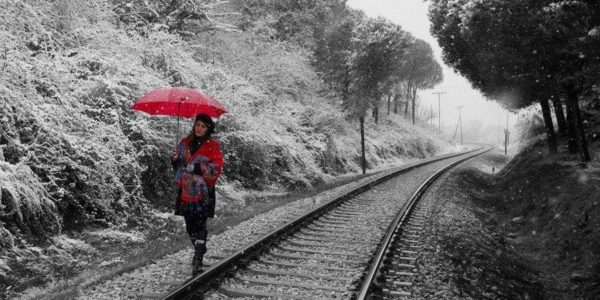 женщина в красном идет вдоль железнодорожных рельс