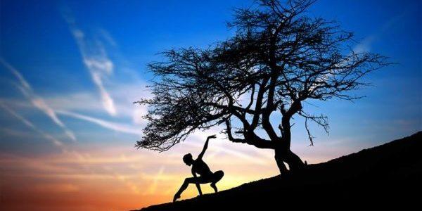 силуэт женщины, делающей какие-то упражнения, на фоне заката